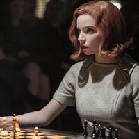 Le personnage Beth Harmon est attablé devant un jeu d'échecs.