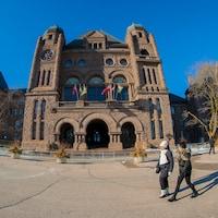 Deux femmes marchent en hiver devant l'édifice de l'Assemblée législative de l'Ontario.