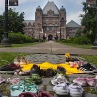 Des chaussures d'enfants reposent au pied de la statue de Sir John A. MacDonald, qui se trouve sur le terrain de l'Assemblée législative de l'Ontario à Queen's Park, à Toronto, le vendredi 18 juin 2021.