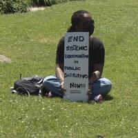 Une manifestante tient une pancarte où il est écrit qu'il faut faire cesser la discrimination systémique au sein des institutions publiques.
