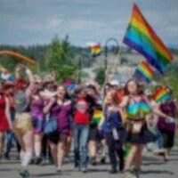 des gens marchant dans la rue, avec des drapeaux LGBT