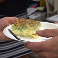 Quelqu'un tend un plat comprenant un morceau de quiche lorraine végétarienne.