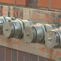 Quatre raccords-pompier sur un mur