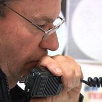 Un homme tient un micro de radio amateur.