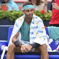 Un joueur patiente sur une chaise en attendant que la pluie cesse.