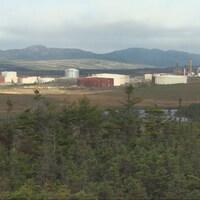 Les bâtiments de la raffinerie. De la vapeur sort des cheminées.