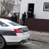 Quatre policiers rentrent dans une petite maison.