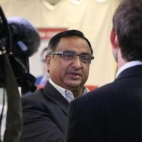 Le portrait d'un homme qui discute avec un journaliste.