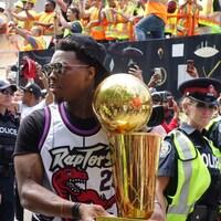 Il tient le trophée pendant le défilé.