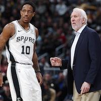 Le joueur de basketball DeMar DeRozan accompagné de l'entraîneur-chef des Spurs, Gregg Popovich.