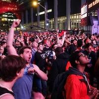 Une foule regarde l'écran où est diffusé le match des Raptors lors du premier match de la finale avec des personnes qui crient et ont le poing levé.