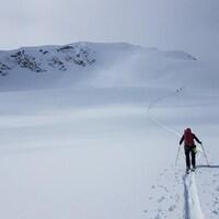 Une personne fait du ski de randonnée dans une montagne enneigée de la C.-B.