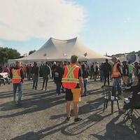 Des employés en grève sont rassemblés près d'une grande tente blanche.