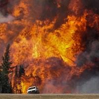 Un énorme feu de forêt fait rage tout près d'une camionnette.