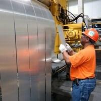Un travailleur inspecte une feuille d'aluminium.