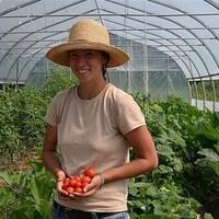 La jeune agricultrice dans sa serre avec des tomates dans les mains