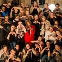 Une trentaine de personnes rassemblées mettent leurs mains en forme de coeur.