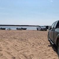 Des camions et des chaloupes sur une plage.
