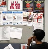 Une dame regarde un tableau d'affichage sur lequel des emplois sont proposés