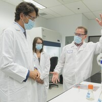 Le premier ministre du Canada Justin Trudeau s'entretient avec des chercheurs en blouse blanche dans un laboratoire.