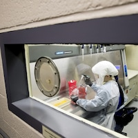 Une femme portant un habit de protection manipule des instruments de laboratoire.