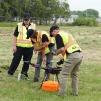 Quatre hommes sont autour d'un drone dans un vaste espace gazonné.