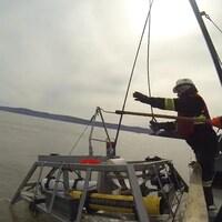 Des scientifiques sur un bateau déposent des instruments de mesure dans la mer.