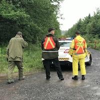 Trois policiers de dos, devant un véhicule de la SQ. Ils sont sur une route de campagne, avec des boisés autour.