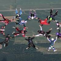Une quinzaine de femmes sautent en parachute en formation, se tenant par la main.