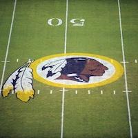 Un terrain de football où le logo des Redskins représentant un Autochtone et des plumes a été peint.