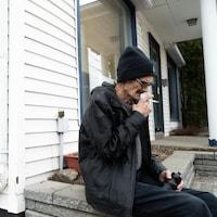 Un homme fume une cigarette à l'extérieur d'un établissement.