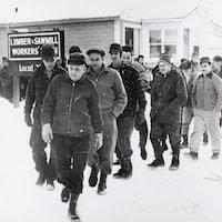 """Photographie noir et blanc d'hommes qui marchent en file devant une enseigne où est écrit """"Lumber and Sawmill Workers' Union""""."""