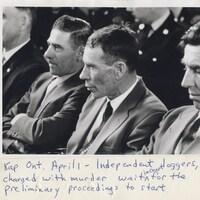 Photographie noir et blanc de trois hommes à l'air sérieux assis un à côté de l'autre.