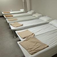 Une rangée de lits dans un dortoir d'un refuge.