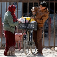 Une femme et son fils lestent de la nourriture dans un panier de bicyclette, alors qu'un homme marche devant eux avec une boîte d'aliments.