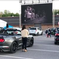 Une femme regarde un film sur écran géant dans un stationnement.