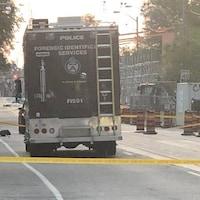 Un camion de police et des banderoles jaunes bloquent la rue.