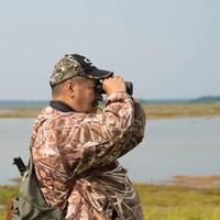 Un homme portant une casquette et un sac à dos regarde au loin grâce à des jumelles. Derrière lui, une étendue d'eau et une parcelle de forêt.