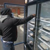 Un homme choisit un repas dans un réfrigérateur à l'extérieur.
