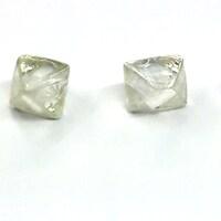 Trois diamants bruts sont posé sur une table.