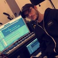 René-Charles Angélil est assis devant un ordinateur qui affiche un logiciel de production musicale dans un studio.