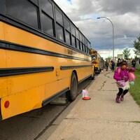 Une élève vient de débarquer d'un bus scolaire. Elle porte un masque jaune et se dirige vers l'entrée de l'école primaire Father Leo Green à Edmonton. Un groupe d'autres personnes se trouve derrière elle.