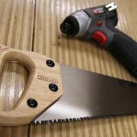 Une scie et une perceuse sur une table en bois.