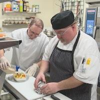 Deux personnes s'affairent à la préparation de repas dans une cuisine.