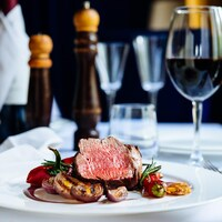 Une assiette de bœuf et de légumes et un verre de vin rouge sur une table de restaurant