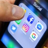 Un homme tient un téléphone intelligent avec les icônes des applications de réseaux sociaux Facebook, Instagram et Twitter vues sur l'écran à Moscou.