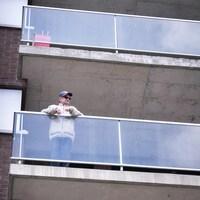 Un homme âgé sur son balcon.