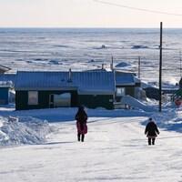 Une femme et sa fille marchent dans la rue de Resolute qui, au loin, donne sur la baie de Resolute et l'étendue de l'Arctique.