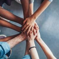 Six personnes unissent leurs mains les unes sur les autres.