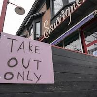 Une affiche dit « mets à emporter seulement » devant un restaurant.